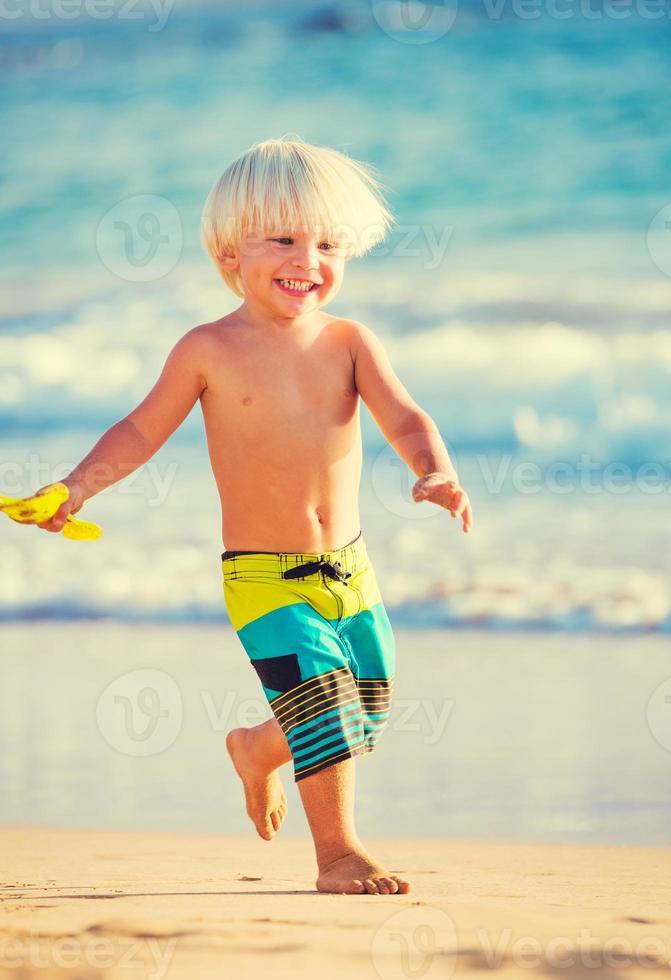 jongen speelt op het strand foto