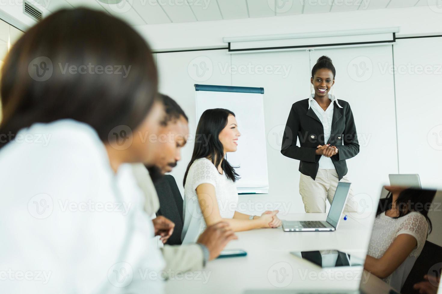 jonge mensen uit het bedrijfsleven zitten aan een vergadertafel en leren foto
