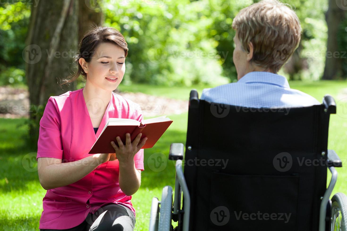 verpleegkundige leest naast gehandicapte vrouw foto