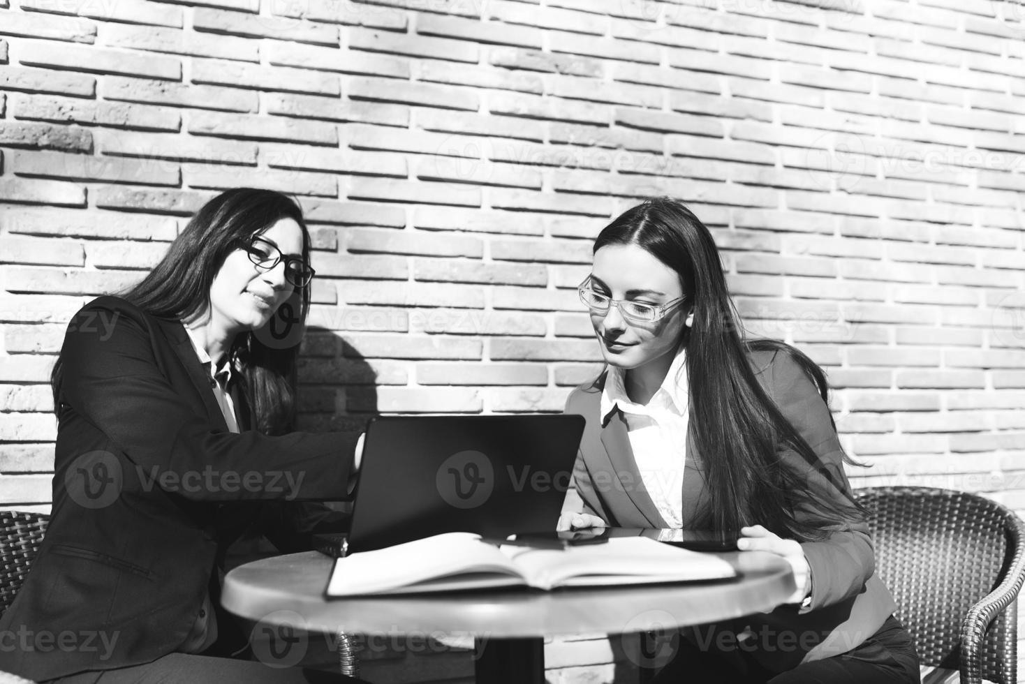 twee vrouwelijke ondernemers kijken naar een laptop teamwerk doen foto