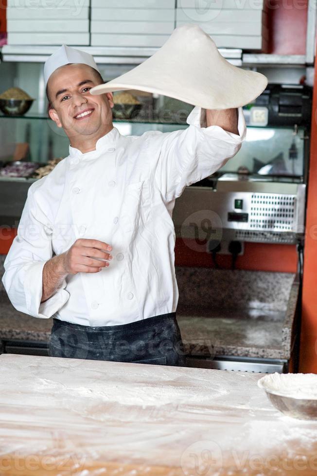 chef-kok het pizzadeeg gooien foto