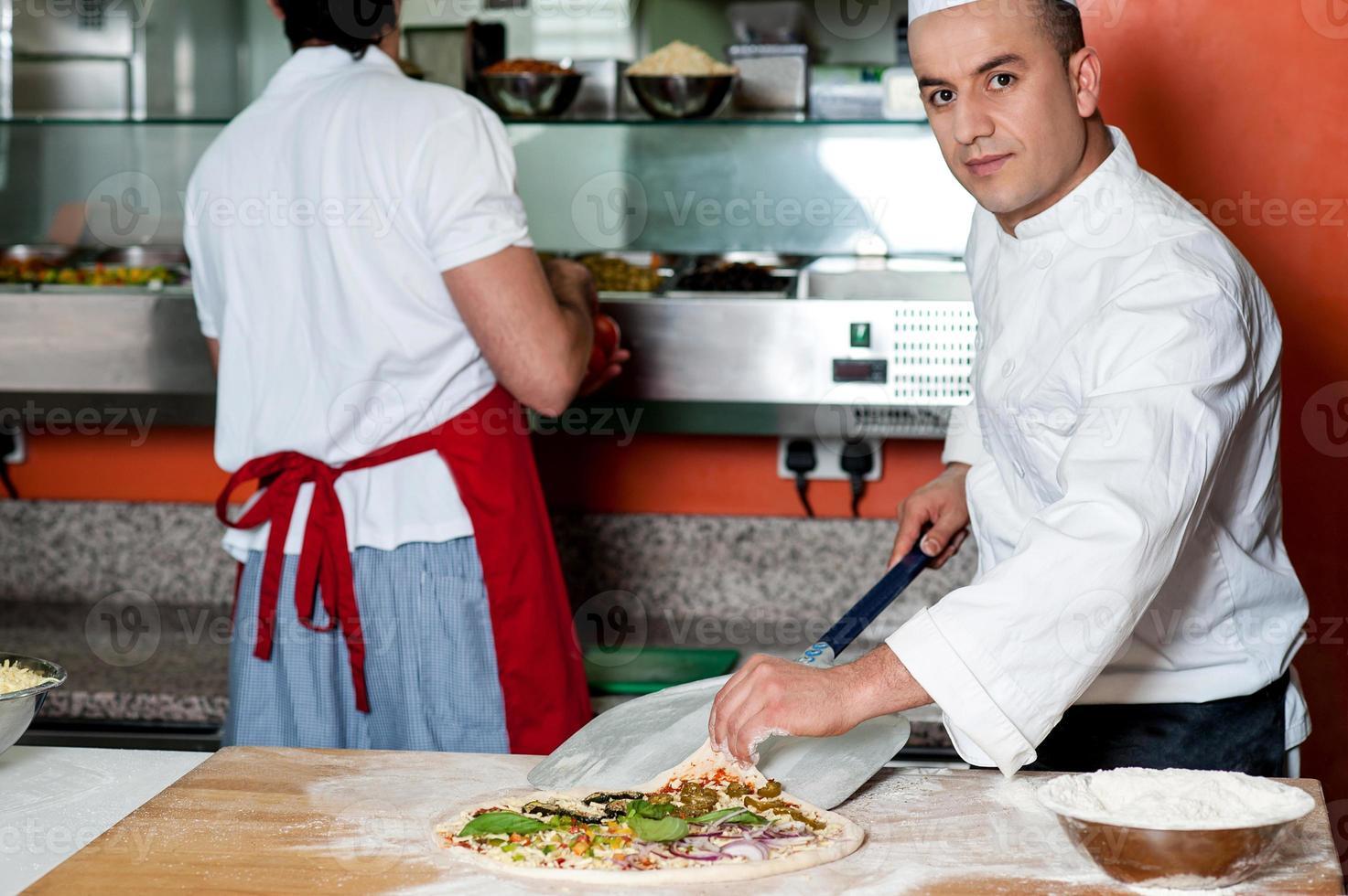 chef-kok die laatste aanraking geeft aan plantaardige pizza foto