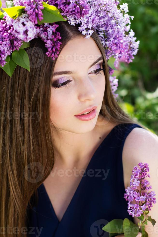 mooi meisje met krans van lila bloemen foto