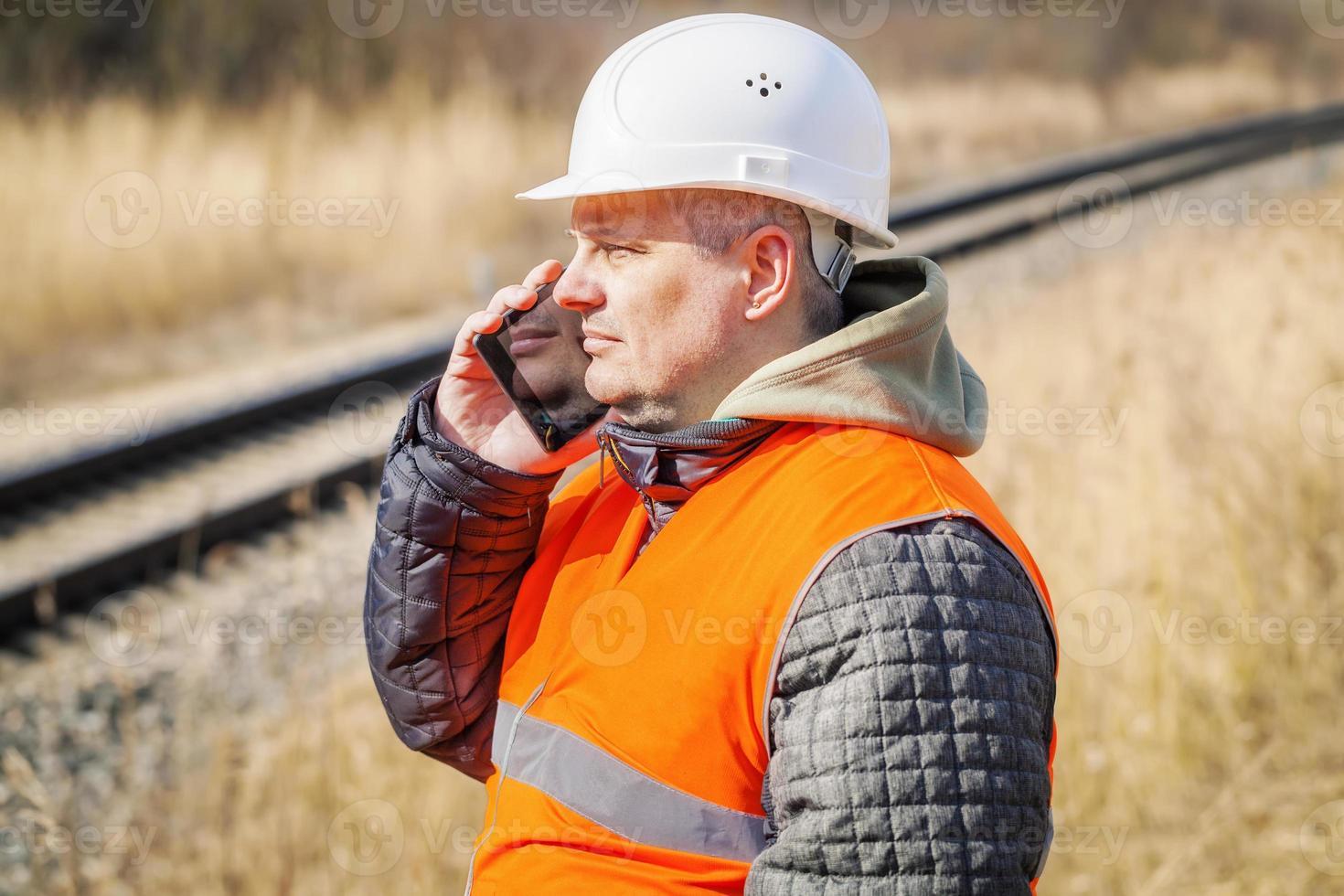 spoorwegmedewerker die op celtelefoon dichtbij spoorweg spreekt foto