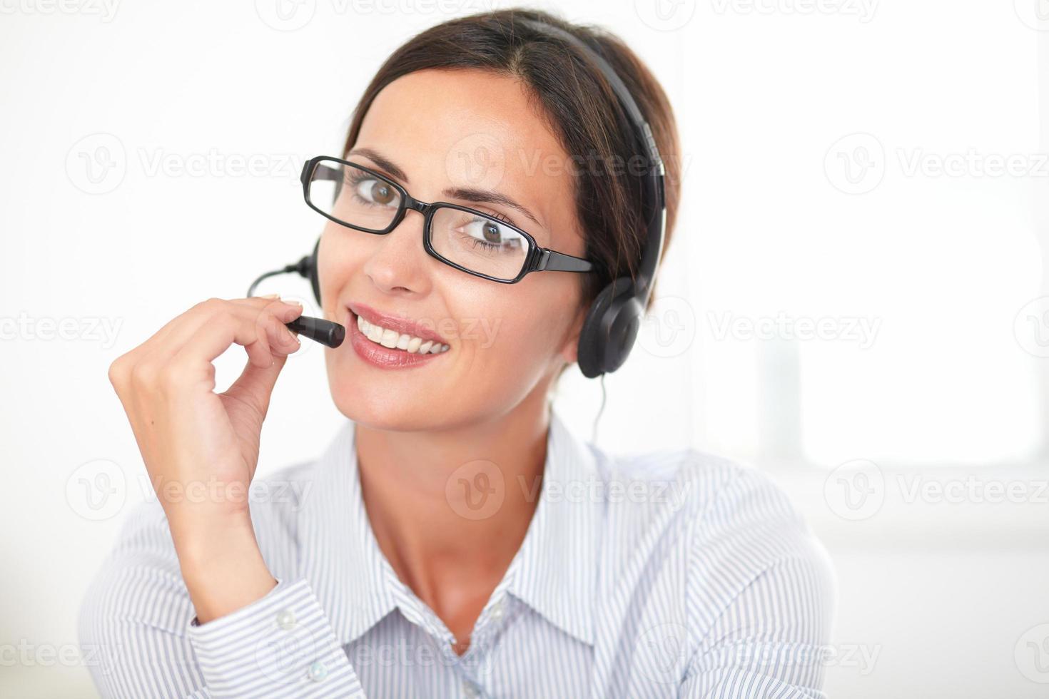 jonge bedrijfsmedewerker die op hoofdtelefoons spreekt foto