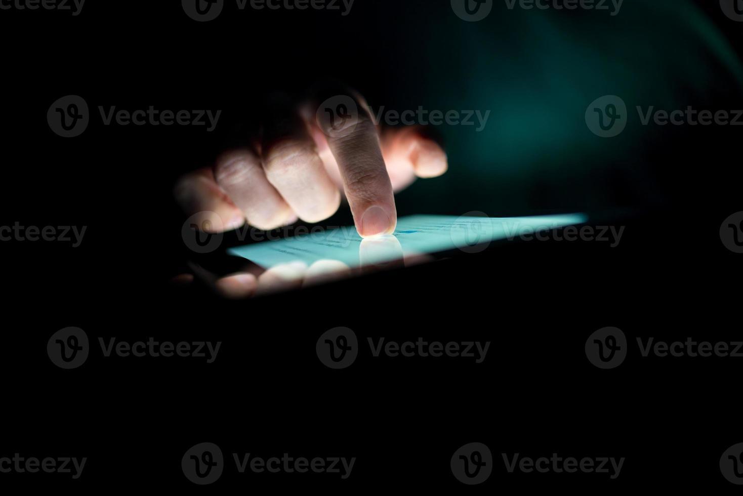 man met een tablet in het donker foto