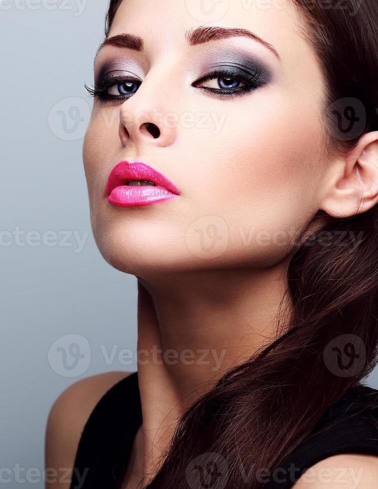 mooie vrouw met heldere smokey make-up ogen en roze lippenstift foto