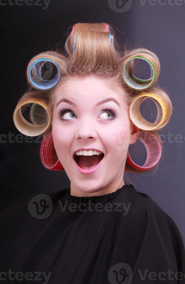 vrolijk gelukkig blond meisje haar krulspelden rollen kapper schoonheidssalon foto