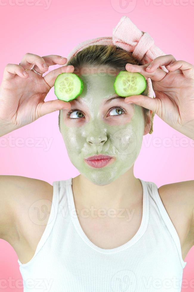 grappige vrouw die een groen gezichtsmasker en komkommers draagt. foto