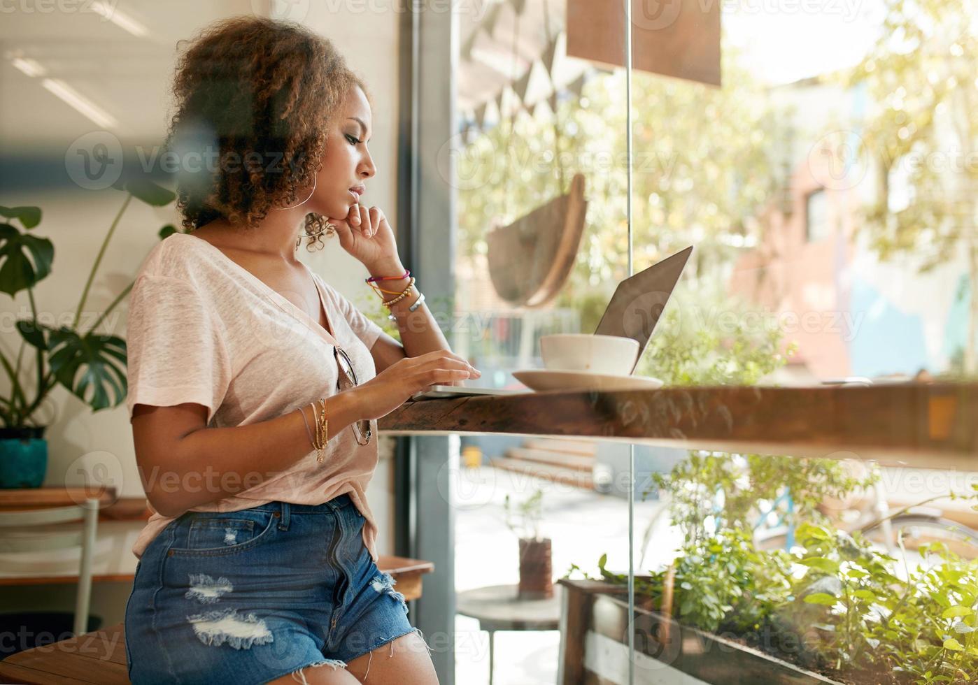 jonge vrouw met behulp van haar laptop in een koffieshop foto