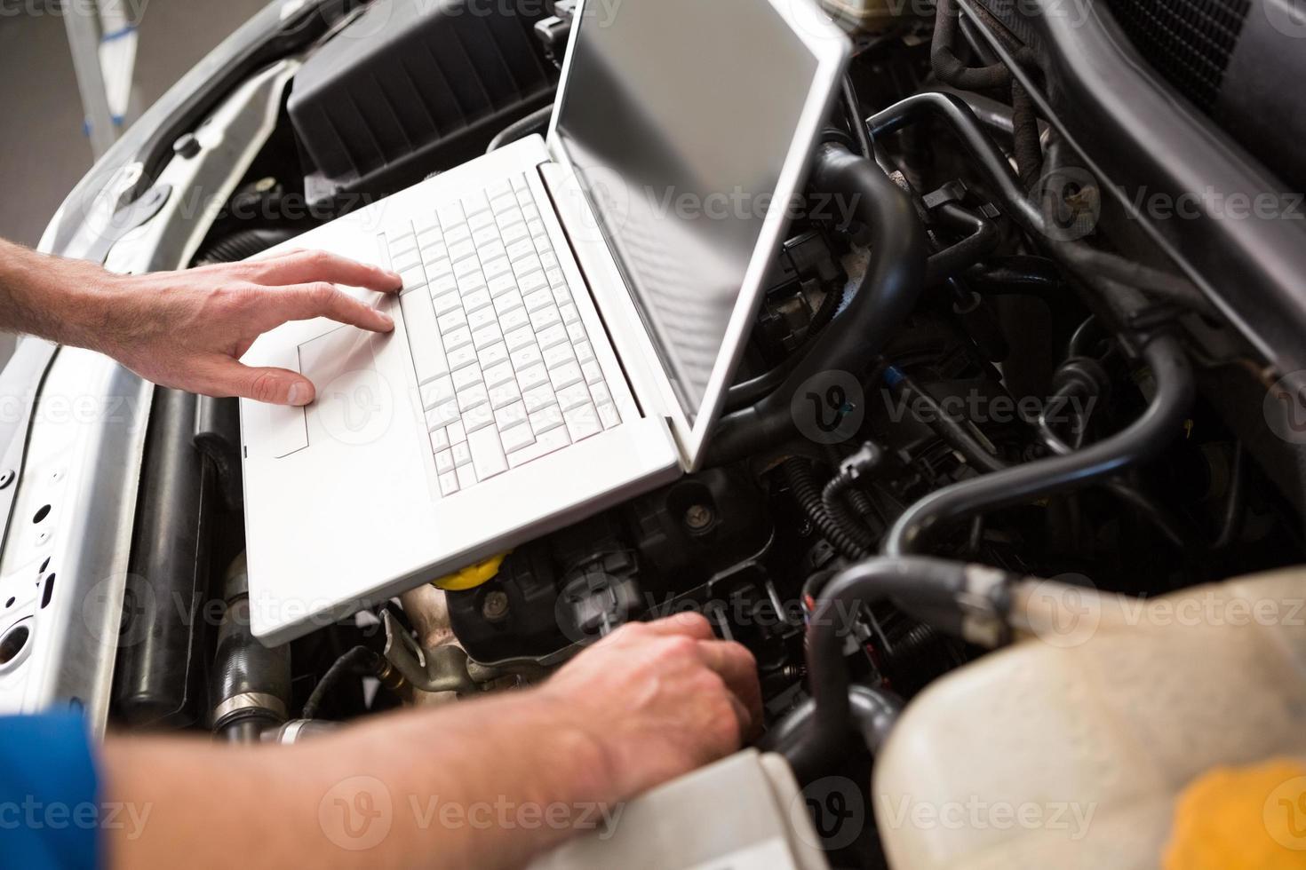 monteur met behulp van laptop op auto foto