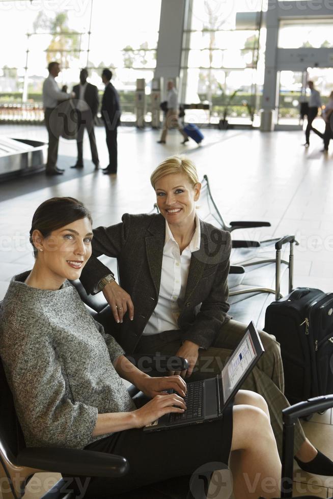 twee vrouwelijke ondernemers wachten in luchthaven vertrekhal, vrouw usi foto