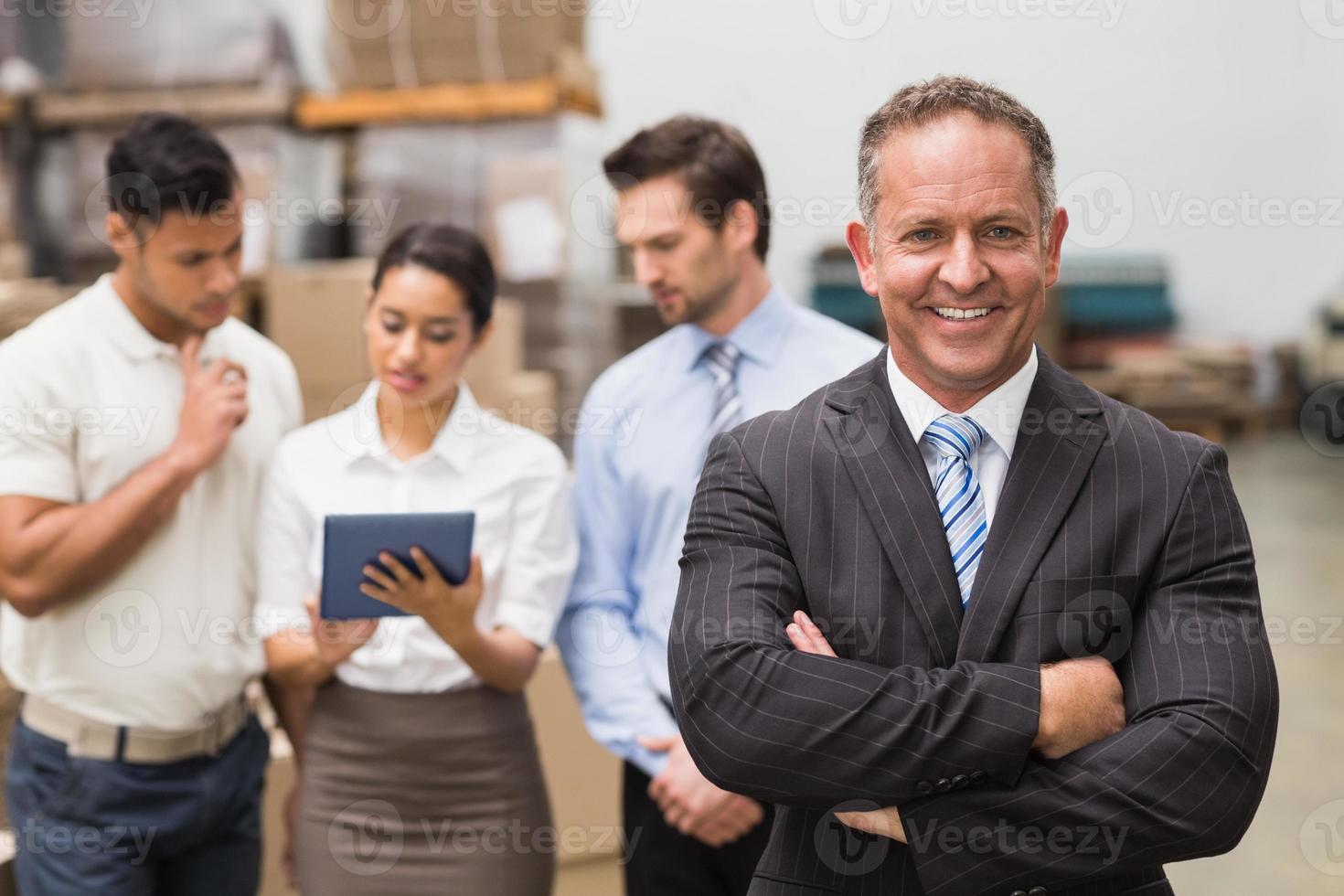 baas staande met gekruiste armen voor zijn werknemers foto