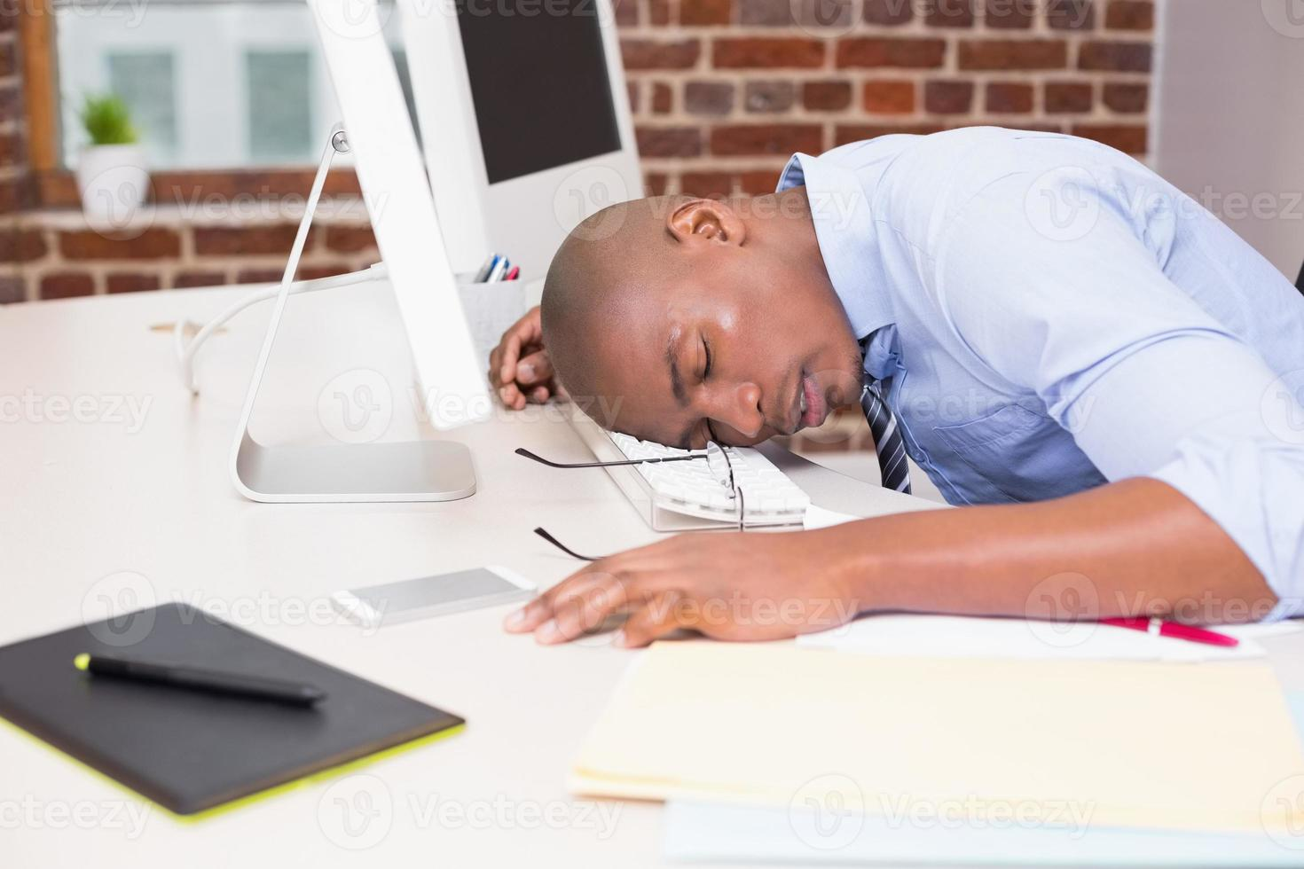 zakenman hoofd rustend op computertoetsenbord foto