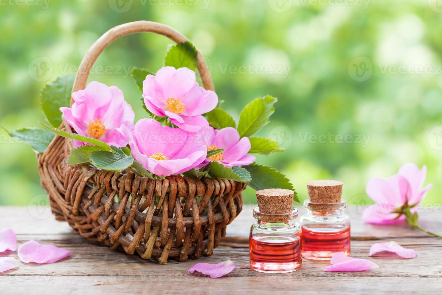 mand met roze rozenbottel bloemen en flessen olie foto