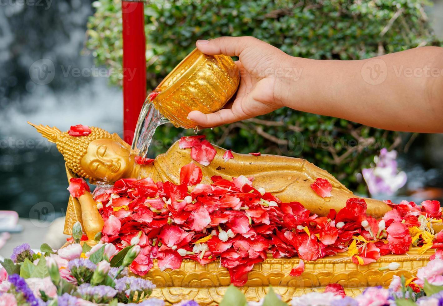 water over Boeddha gieten foto