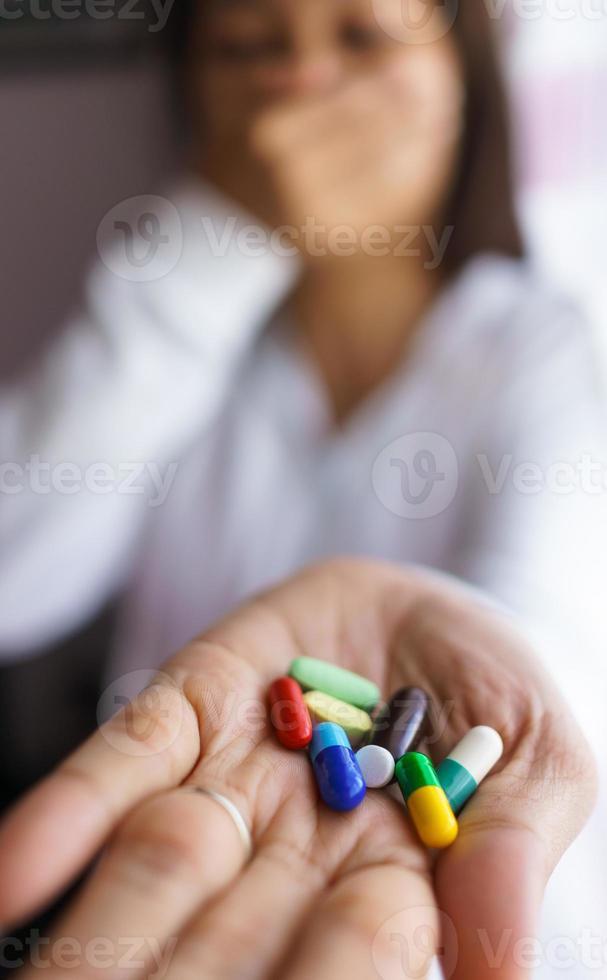 vrouw met medicijnen in haar hand foto