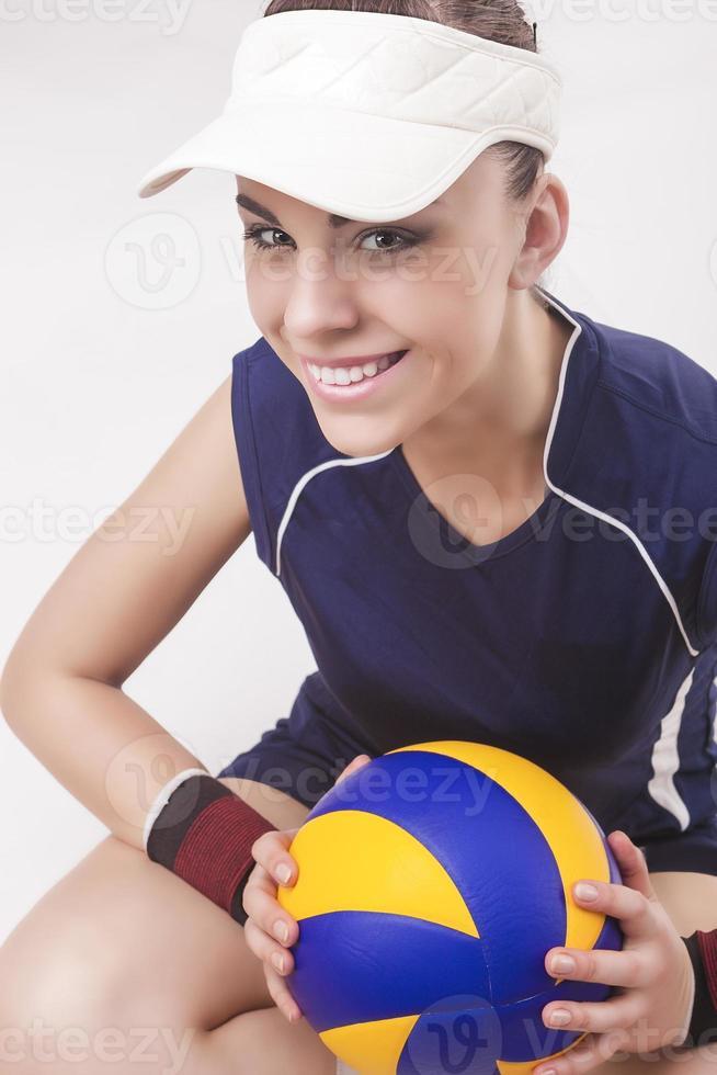 portret van glimlachende Kaukasische professionele vrouwelijke volleyballer in volleybal outfit foto