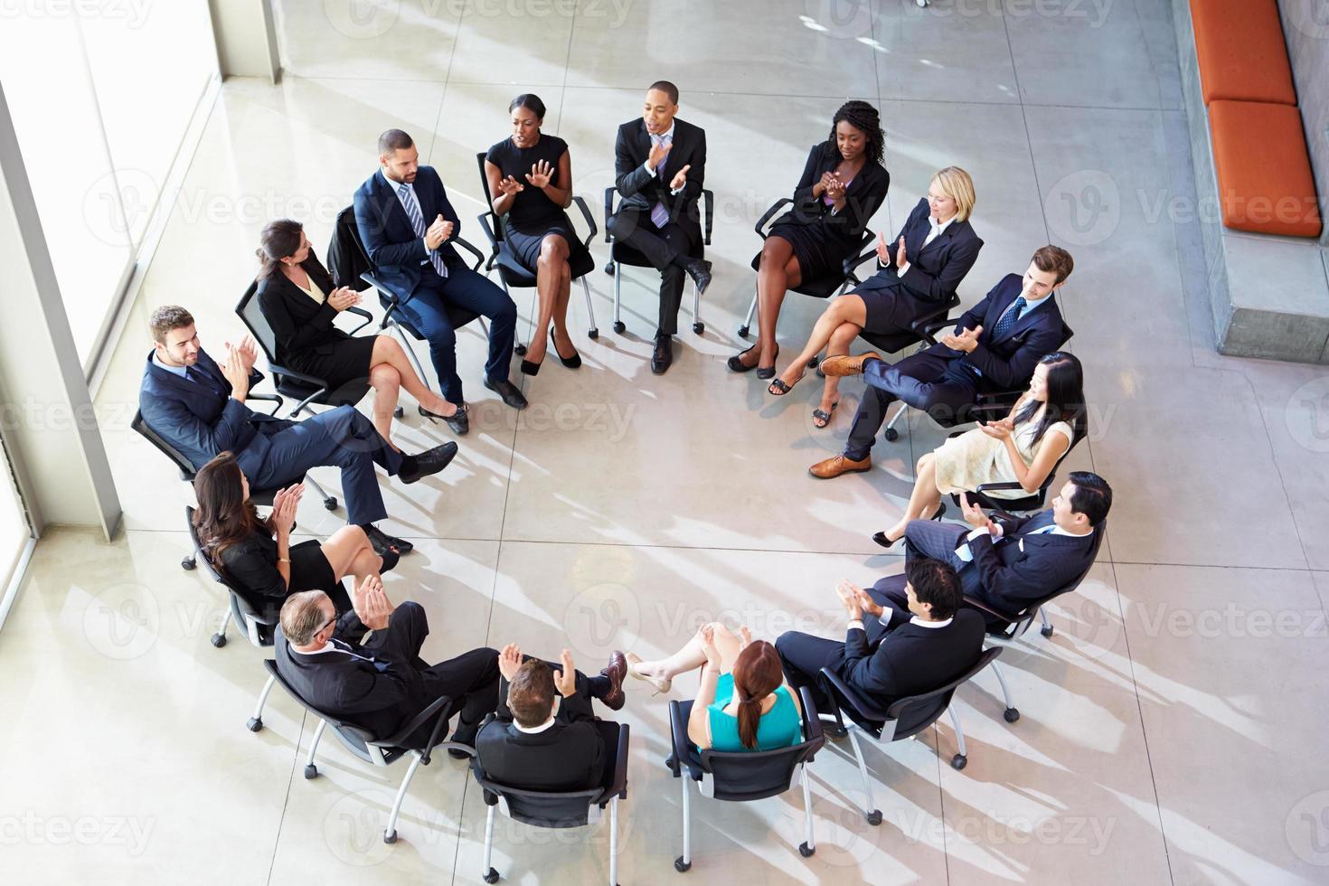 multicultureel kantoorpersoneel applaudisseert tijdens meeting foto