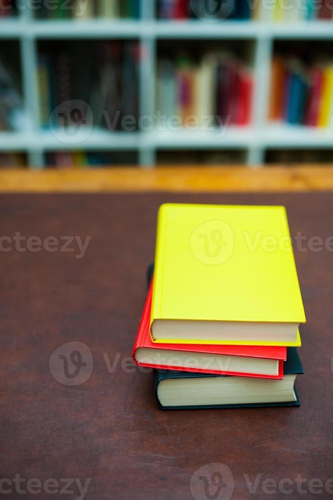 stapel gekleurde boeken op houten bureaublad foto