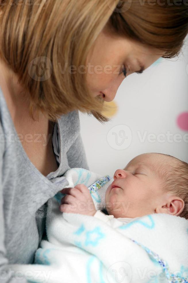 kleine pasgeboren babyjongen in moeders armen foto