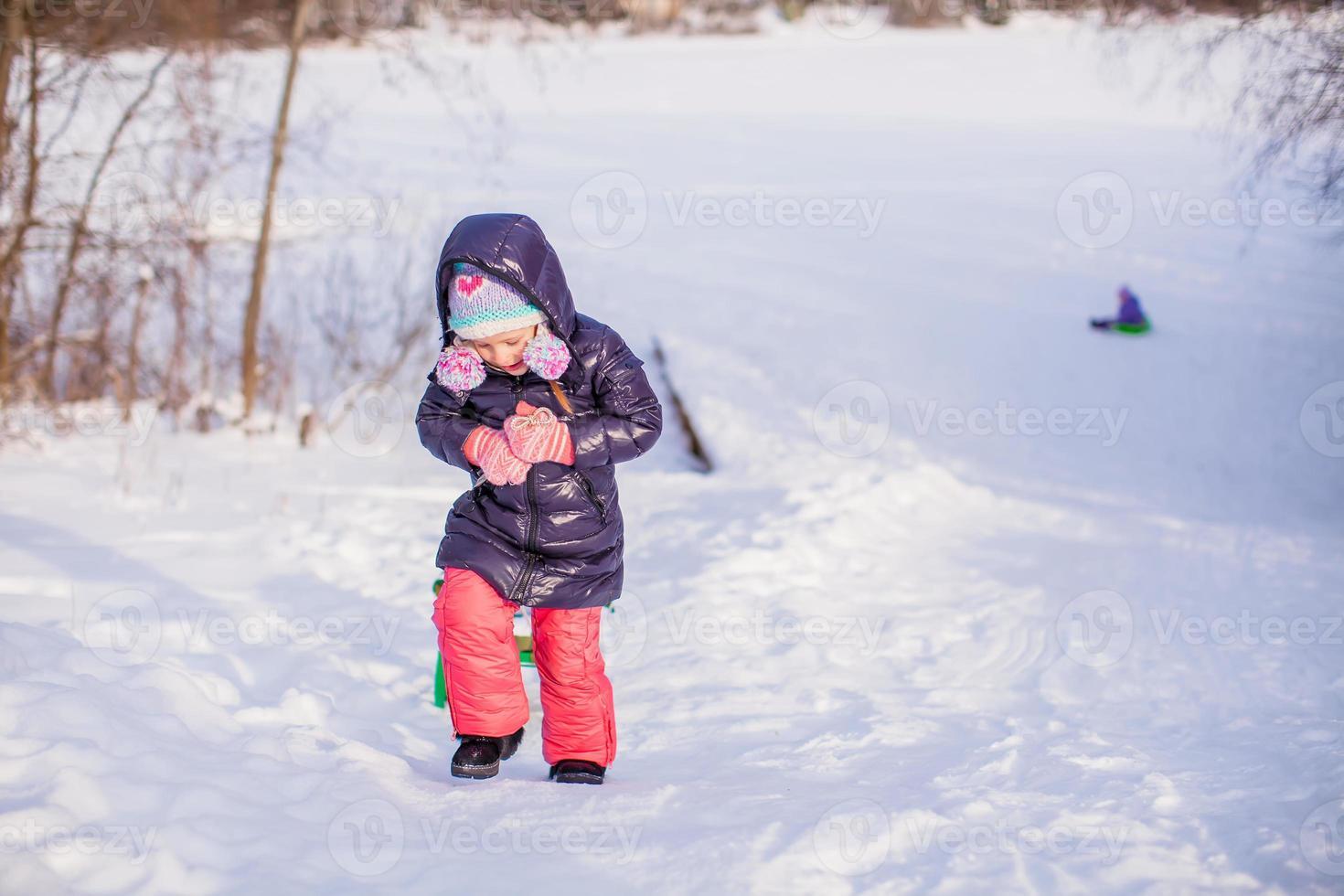 klein schattig gelukkig meisje genieten van sneeuw zonnige winterdag foto