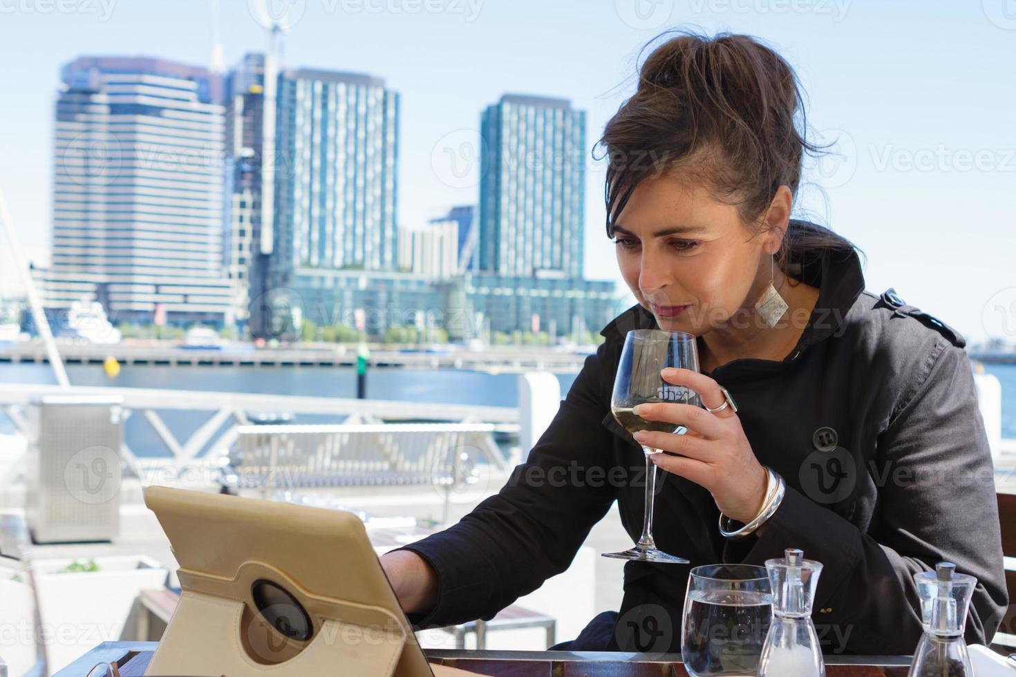 zakelijke vrouw genieten van lunch buiten het lezen van tablet h foto