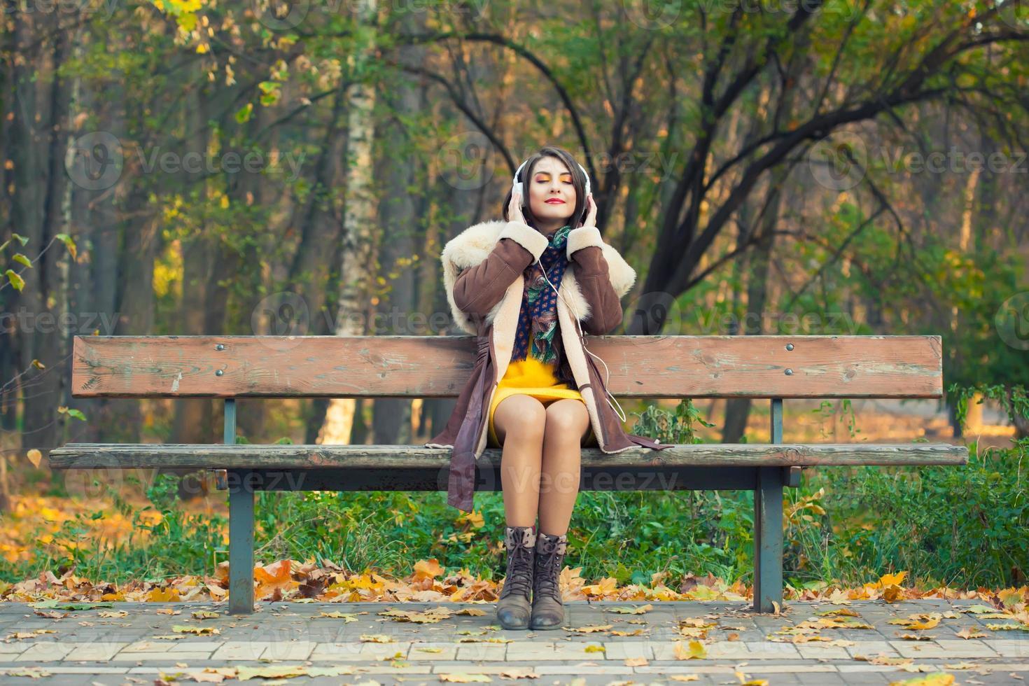 jonge vrouw genieten van een muziek in de herfst seizoen foto