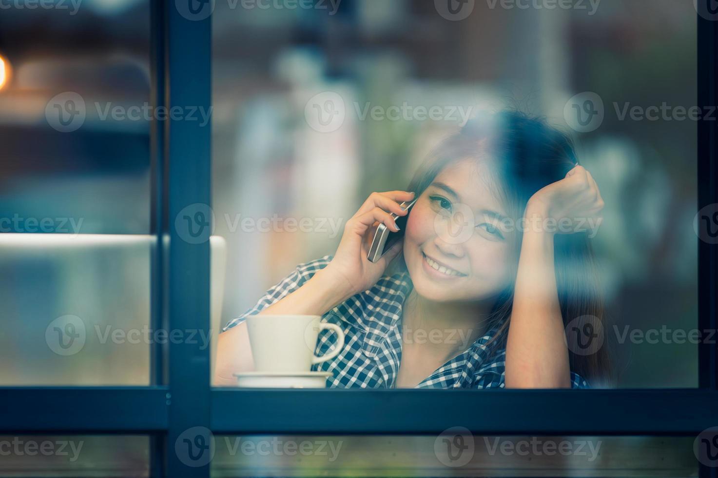 Gelukkige vrouw Azië praten telefoon in café en genieten van koffie foto