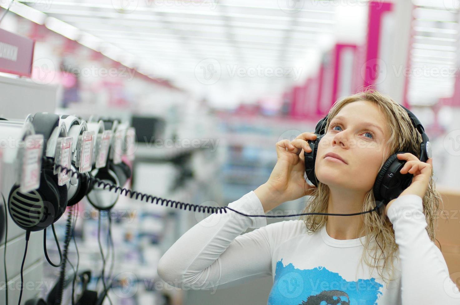 jong meisje luistert naar leuke muziek in een winkel foto