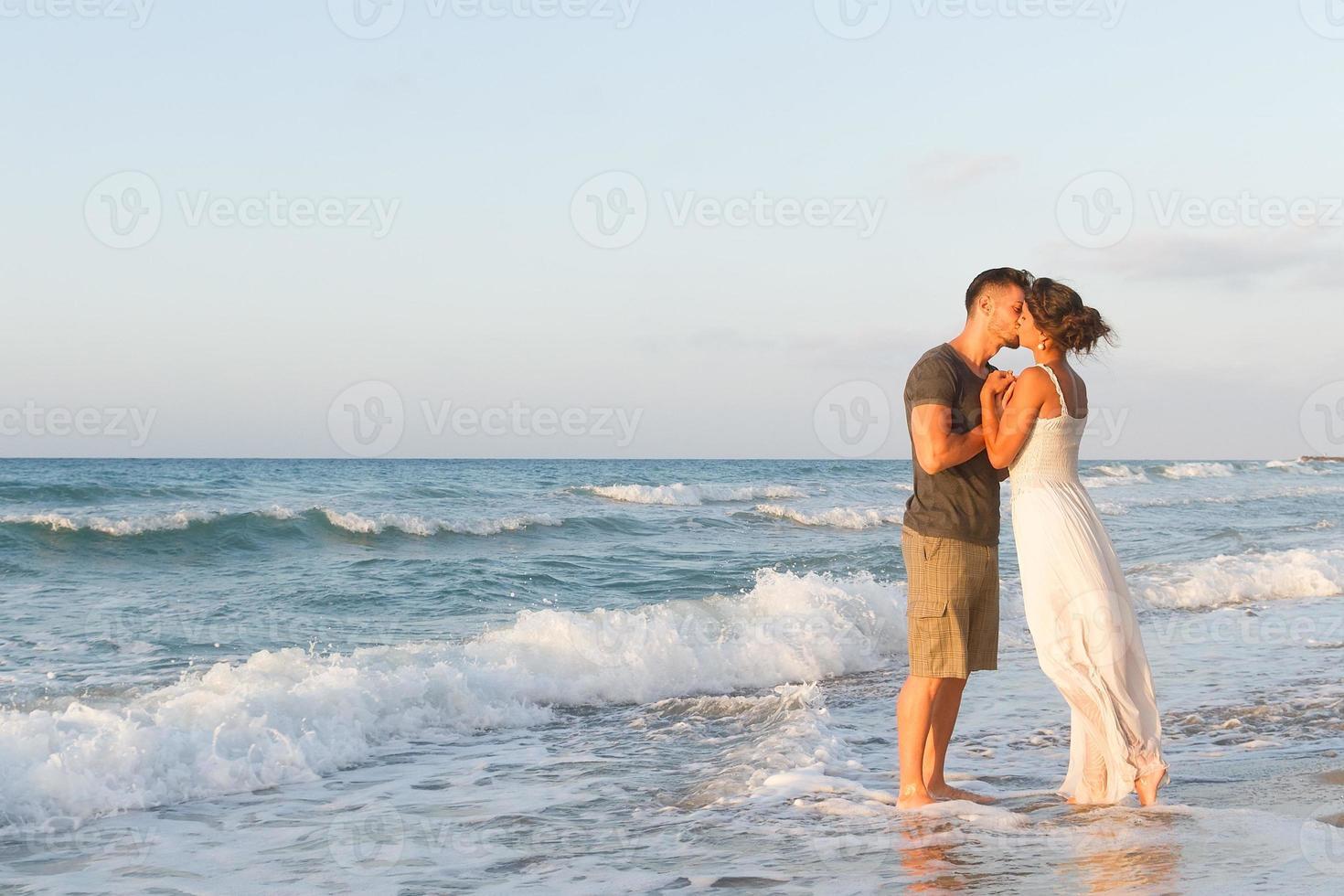 jong stel geniet van wandelen op een wazig strand in de schemering foto