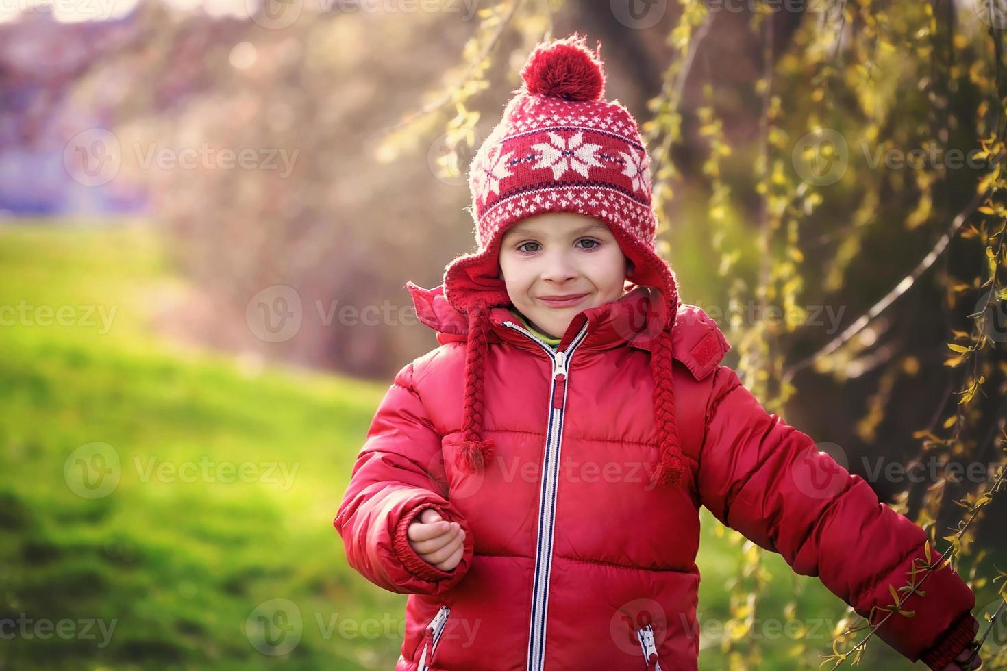 grappige kleine jongen, genieten van zonnige lentedag in het park foto