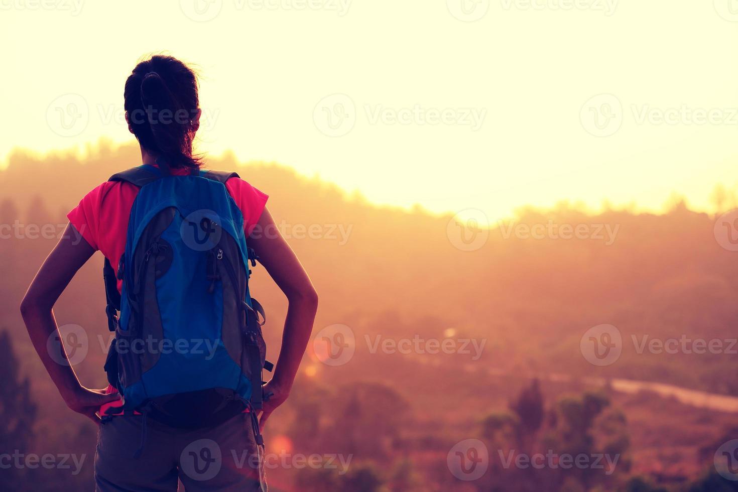 jonge vrouw wandelaar genieten van het uitzicht op zonsopgang bergtop foto