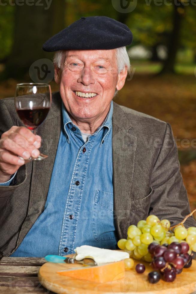 Franse man genieten van rode wijn en kaas in herfst bos. foto