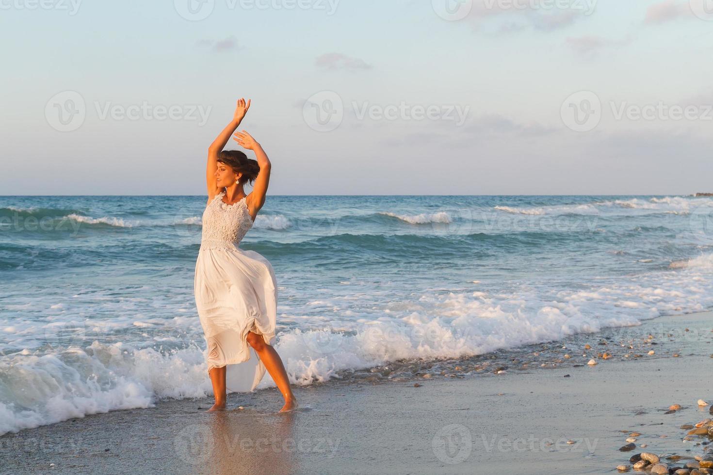 jonge vrouw geniet van een wandeling op het strand in de schemering. foto