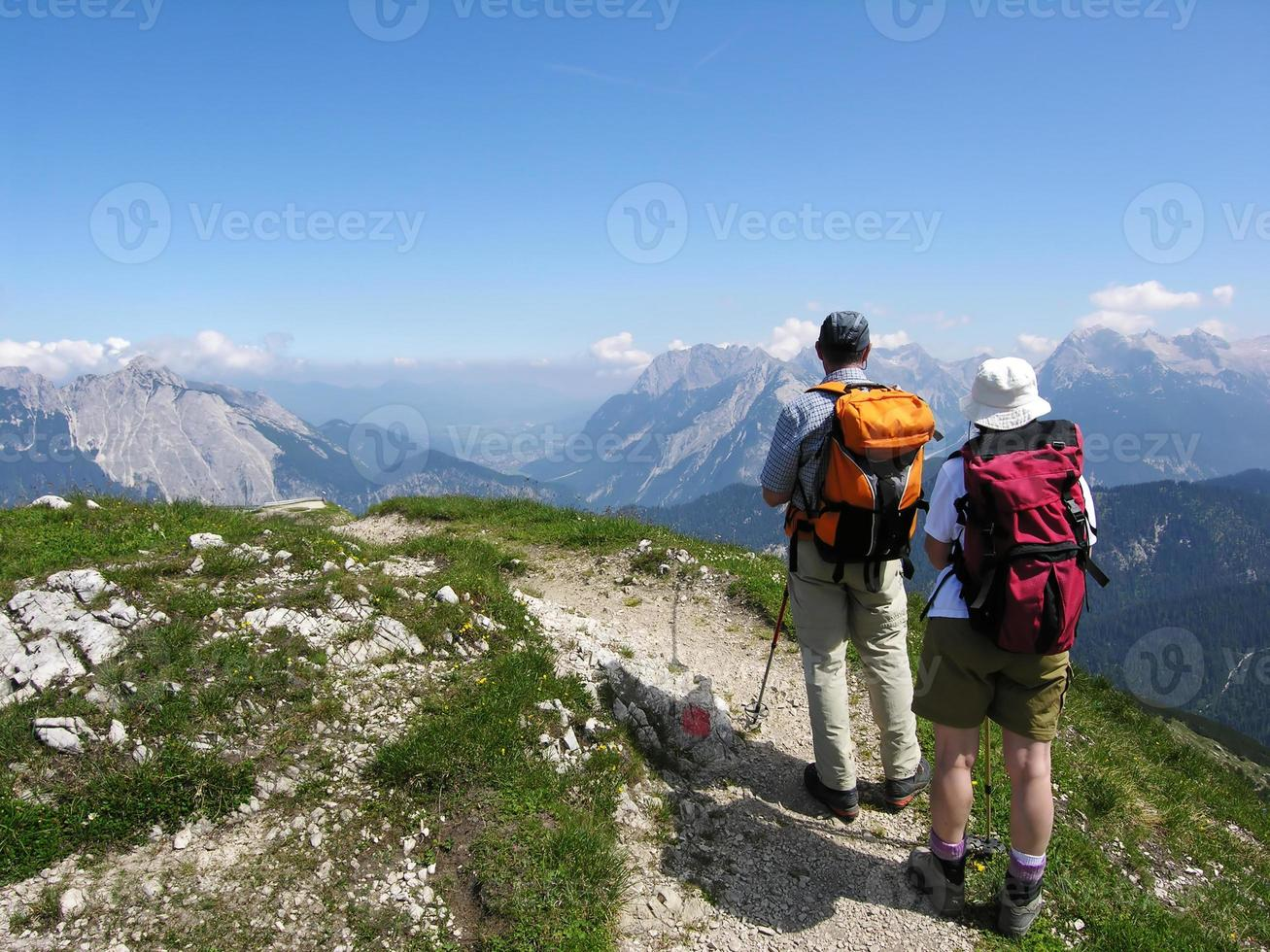 wandelaars op de berg genieten van uitzicht voordat ze weer naar beneden gaan foto