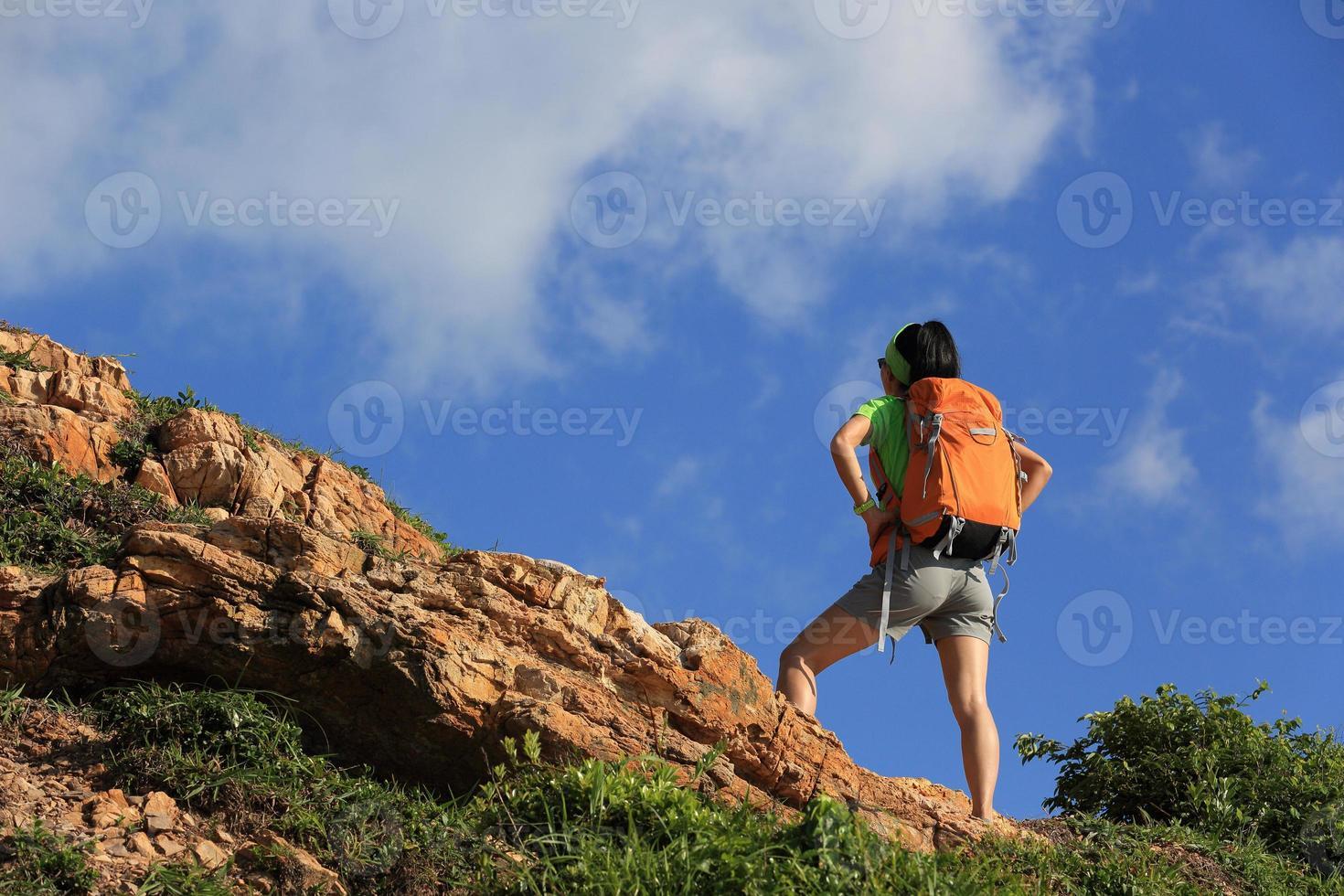 juichende jonge vrouw backpacker geniet van het uitzicht op de bergtop foto