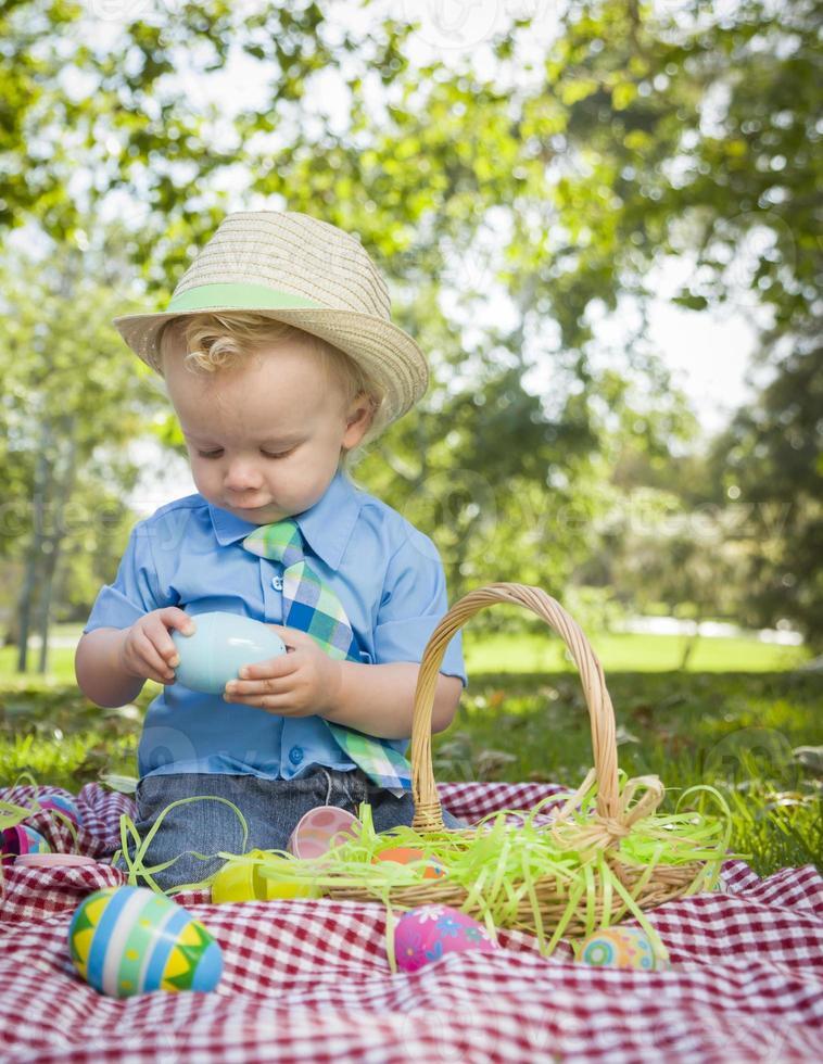 schattige kleine jongen genieten van zijn paaseieren buiten in park foto
