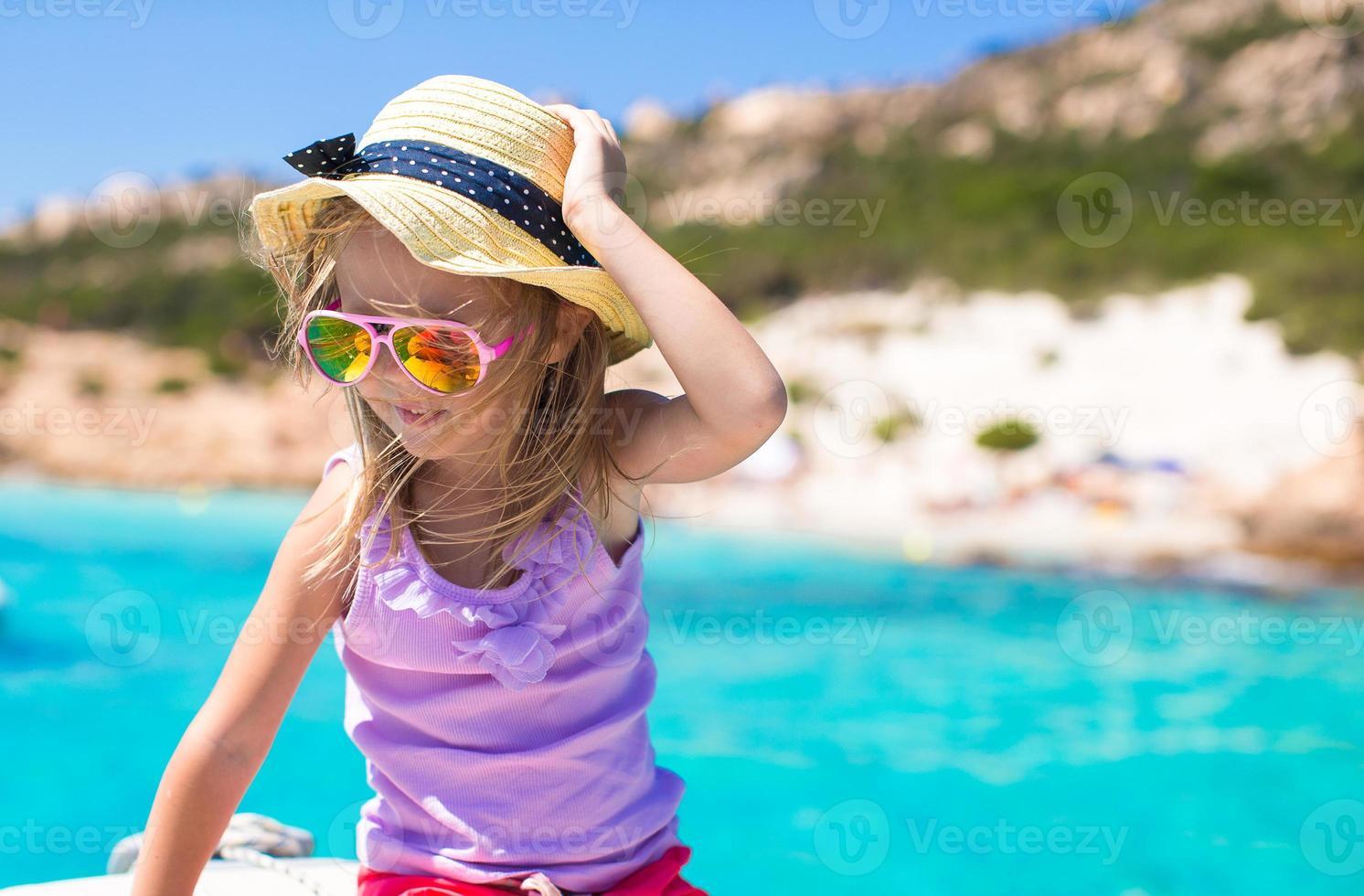 schattig klein meisje genieten van zeilen op boot in open zee foto