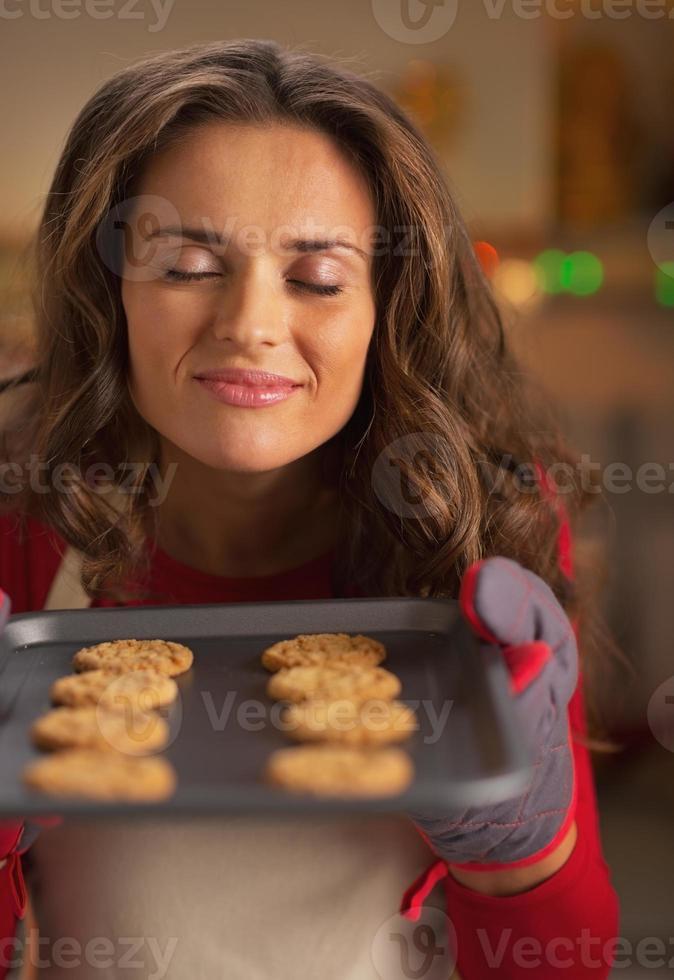 gelukkige jonge huisvrouw genieten van geur van kerstkoekjes op pan foto