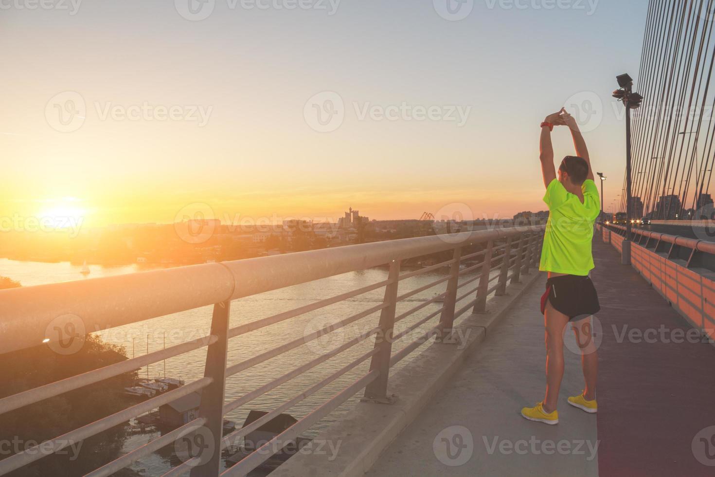 stedelijke jogger die zich uitstrekt over de brug foto