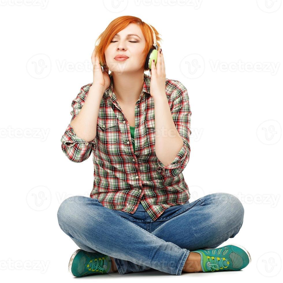het jonge meisje genieten die aan muziek op geïsoleerde hoofdtelefoons luisteren foto