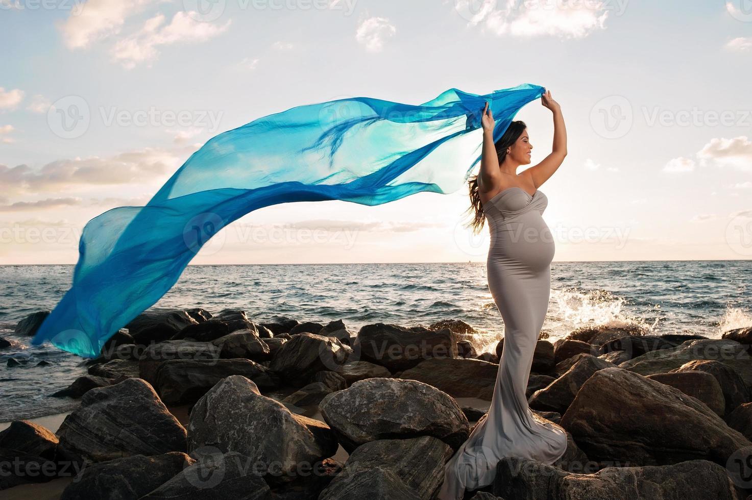 lachende zwangere vrouw op het strand met blauwe sluier foto