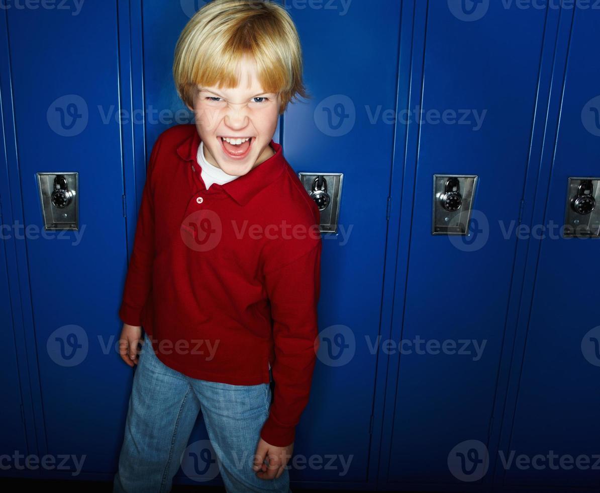 portret van een ondeugende jongen genieten van aganist lockers foto