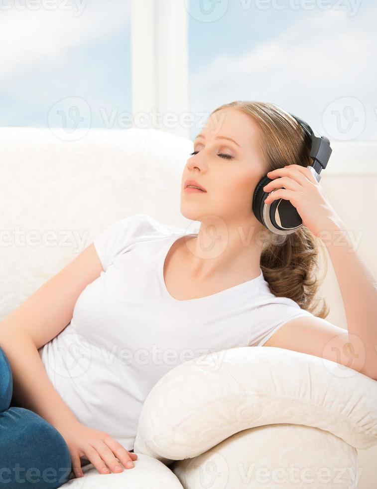 vrouw in koptelefoon geniet thuis van muziek foto