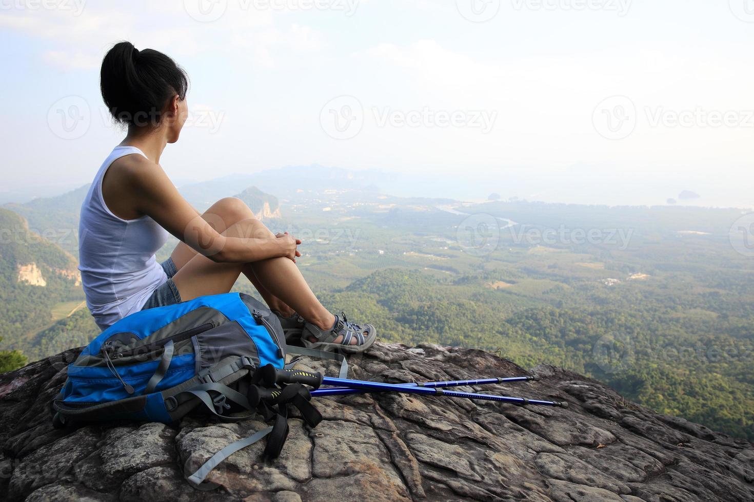 wandelende vrouw genieten van het uitzicht op de bergtop foto