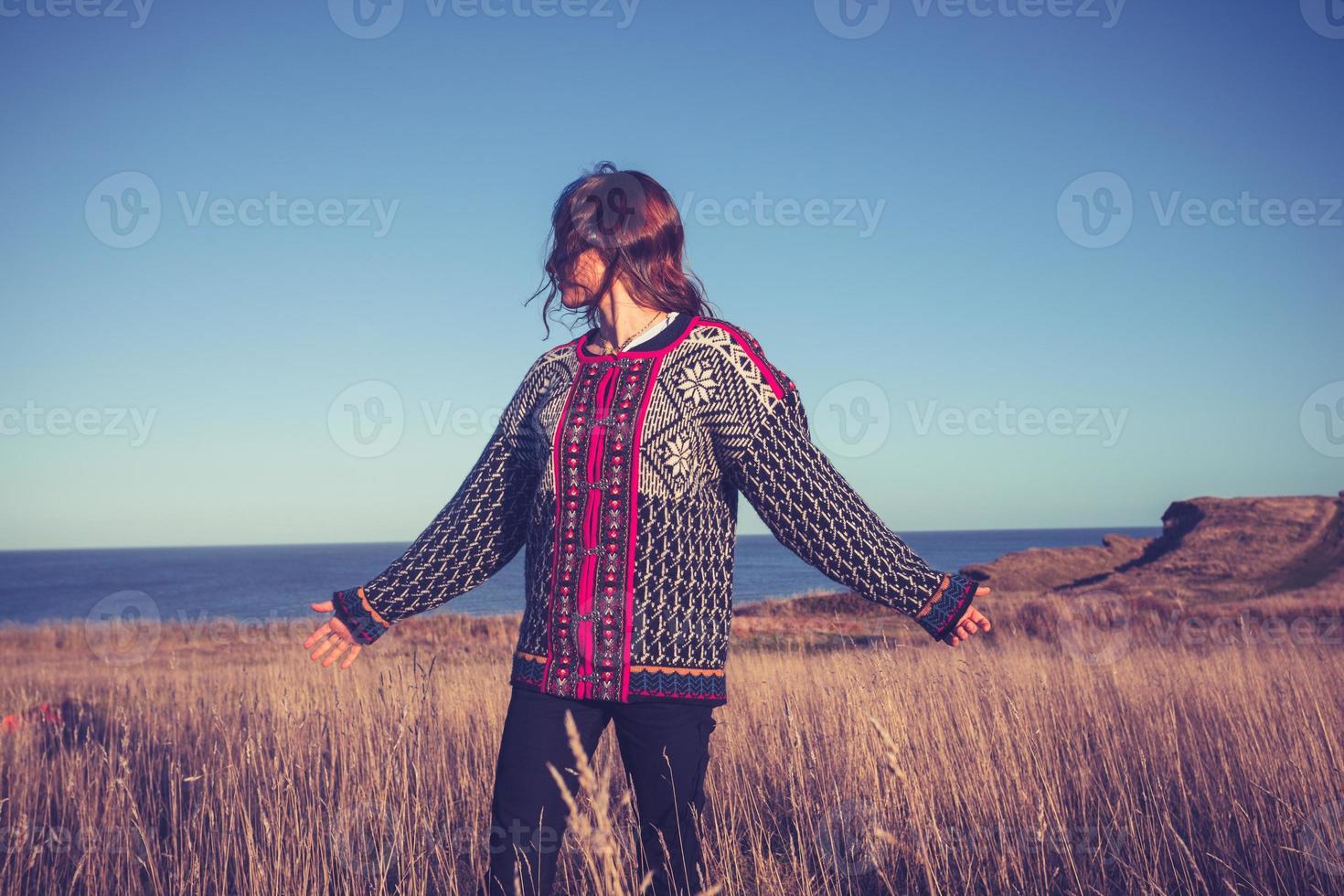 jonge vrouw genieten van vrijheid in de weide aan zee foto