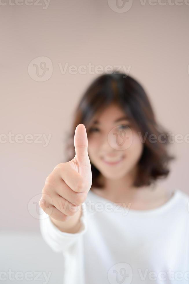 Azië gelukkig lachende vrouw met thumbs up gebaar foto