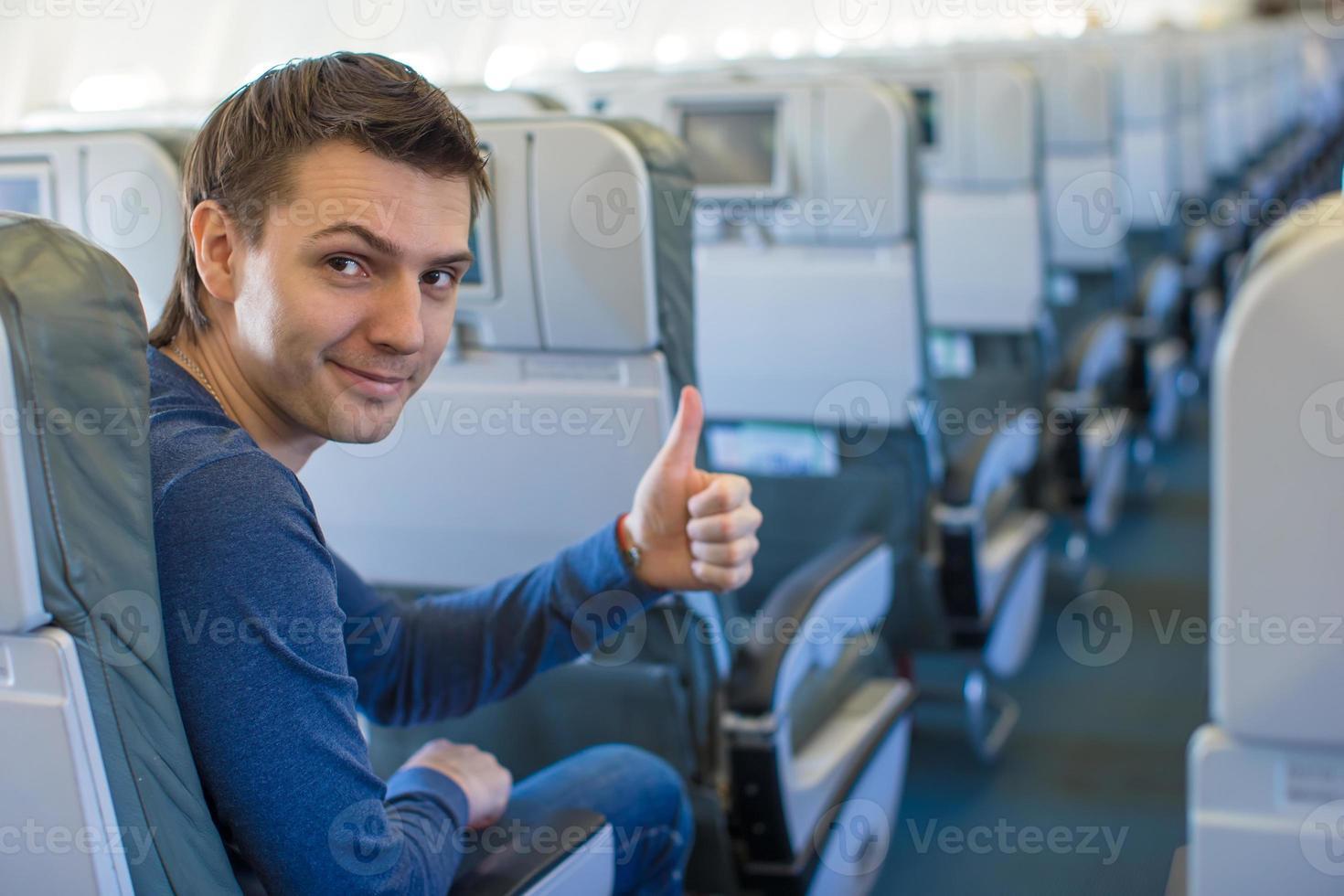 gelukkig man duimen opdagen in het vliegtuig foto