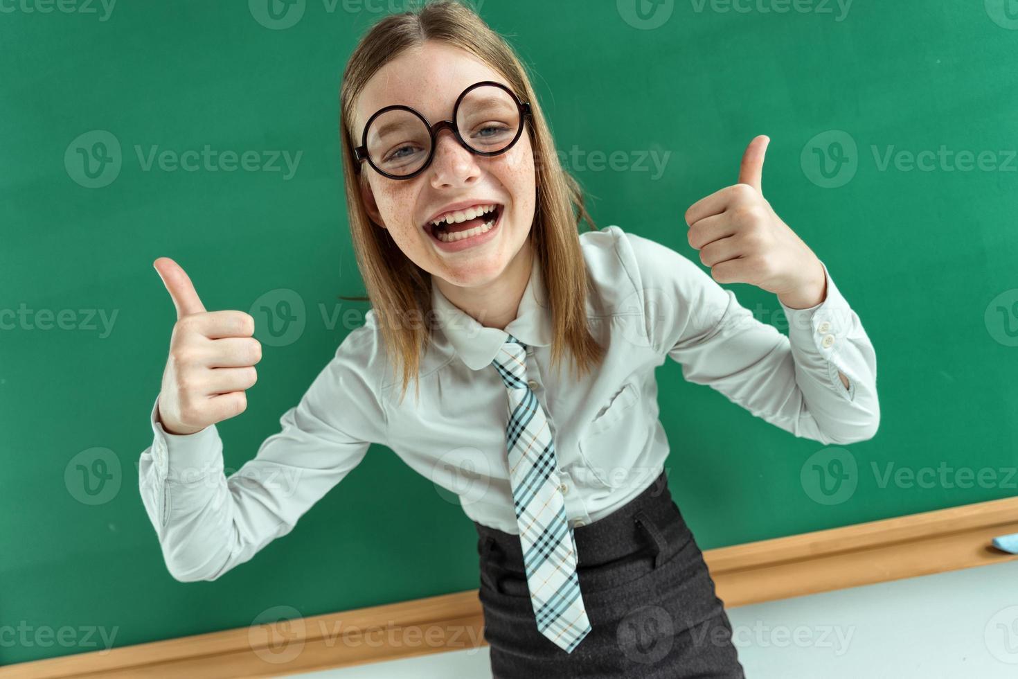 humoristische hoge hoekmening van gelukkig jong schoolmeisje foto
